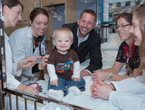 Family-centered rounds at American Family Children's Hospital.  From left: pediatric hospitalist Michelle Kelly, MD; pediatric intern Leslie Riopel, MD; Ayden Hollman and his father Jake; an AFCH pediatric nurse; and senior pediatric resident Jennifer Hartwell, MD.